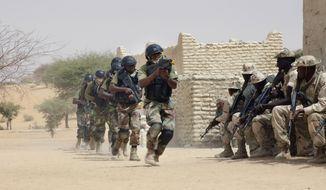 Nigerian special forces run past Chadian troops in an hostage rescue exercise at the end of the Flintlock exercise in Mao, Chad, Saturday, March 7, 2015. The U.S. military and its Western partners conduct this training annually and set up plans long before Boko Haram began attacking its neighbors Niger, Chad and Cameroon. (AP Photo/Jerome Delay)