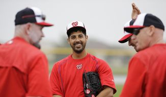 FILE - In this Feb. 25, 2015, file photo, Washington Nationals pitcher Gio Gonzalez, center, stands on the field during a spring training baseball workout in Viera, Fla. A 20-game winner in 2012, the right-hander could be slotted fourth in the rotation behind Max Scherzer, Jordan Zimmermann and Stephen Strasburg. (AP Photo/David Goldman, File)