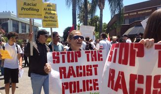 In this July 29, 2012, file photo, protesters demonstrate outside he Anaheim, Calif., Police Department headquarters over a string of recent fatal police shootings in Anaheim. Ferguson, Mo., has become an emblem of the tensions between minorities and police departments nationwide since Darren Wilson, a white officer, shot and killed Michael Brown, an unarmed black teenager, last summer. A U.S. Justice Department report released the first week of March 2015, cleared Wilson of criminal wrongdoing. (AP Photo/The Orange County Register, Stuart Palley, File)