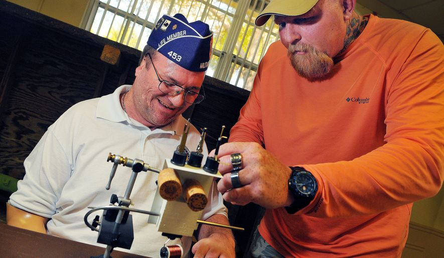 ADVANCE FOR WEEKEND EDITIONS, MARCH 7-8 - In this photo taken Tuesday, Feb. 24, 2015, Amry veteran Russ Marek, of Viera, commander of the Military Order of the Purple Heart chapter in Brevard, does some fly tying with a little help from Army veteran Jason Redler, of Melbourne, during project Healing Waters fly fishing & fly tying held at the Brevard veterans Memorial Center in Merritt Island, Fla. The program helps veterans with PTSD and other issues by teaching them fly tying and fly fishing. (AP Photo/Florida Today, Craig Rubadoux) NO SALES, MAGS OUT