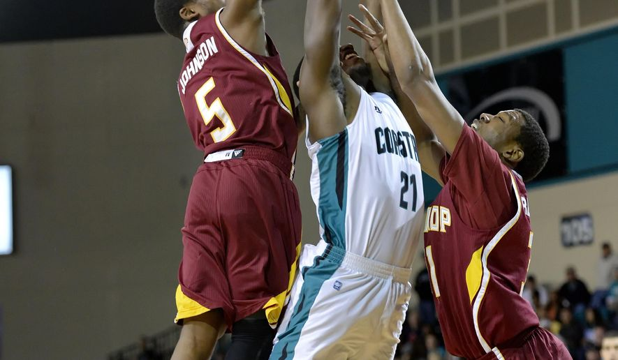 Coastal Carolina's Tristan Curtis, center, pulls in a rebound while defended by Winthrop's Keon Johnson, left, and Tevin Prescott during the first half of the Big South Conference Championship NCAA college basketball game Sunday, March 8, 2015, in Conway, S.C. (AP Photo/Richard Shiro)