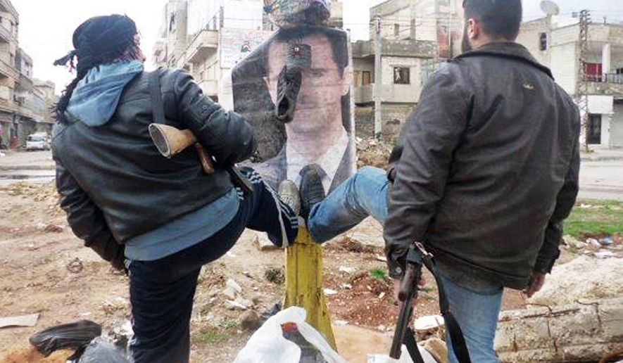 """FILE - In this Tuesday, March. 20, 2012 file citizen journalism image provided by the Local Coordination Committees in Syria and accessed on Wednesday, March 21, 2012, Syrian rebels step on a portrait of Syrian President Bashar Assad in Idlib province, Syria. It began in March 2011 with a few words spray-painted on a schoolyard wall: """"Your turn is coming, doctor."""" The doctor in question was Syrian President Bashar Assad, a trained ophthalmologist whose family has ruled the country for more than 40 years. (AP Photo/Local Coordination Committees in Syria, File)"""