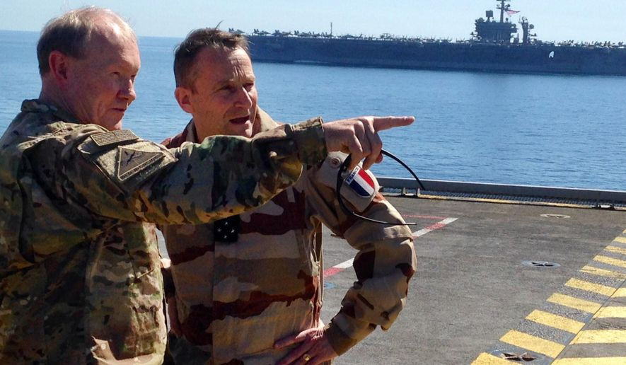 Gen. Martin Dempsey, chairman of the U.S. Joint Chiefs of Staff, left, confers with his French counterpart, Gen. Pierre de Villiers, aboard the French aircraft carrier Charles de Gaulle in the Persian Gulf on Sunday, March 8, 2015. Dempsey says some Iraqi army units in line for U.S.-led training to fight the Islamic State group are showing up ill-prepared. (AP Photo/Bob Burns)