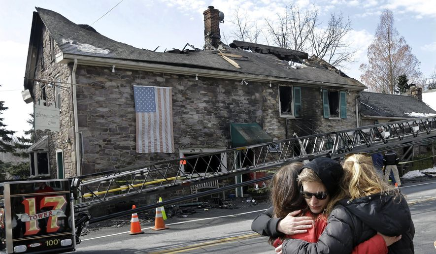 As firefighters and officials investigate an overnight fire that destroyed The Sergeantsville Inn Monday, owner Lisa Clyde, left, is hugged by neighbors March 9, 2015, in Delaware Township, N.J. The fire destroyed the historic New Jersey inn that once hosted George Washington.   (AP Photo/Mel Evans)