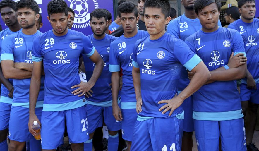 FILE - In this Aug. 20, 2014 file photo, Indian team captain Sunil Chhetri (11) stands with his teammates after their loss in the last match of the two-match friendly soccer tournament between India and Pakistan in Bangalore, India. Both teams will be among 12 squads in Asia to play qualifying matches for the 2018 World Cup this week, the first step on the road to Russia. (AP Photo/Aijaz Rahi, File)