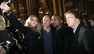 From left, model Cara Delevingne, takes a photographer with actor Woody Harrelson, singers Kanye West and Paul McCartney prior to Stella McCartney's ready to wear fall-winter 2015-2016 fashion collection during Paris Fashion Week, Paris, France, Monday, March 9, 2015. (AP Photo/Thibault Camus)