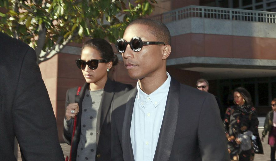 "In this Wednesday, March 4, 2015, photo, Pharrell Williams and an unidentified woman leave Los Angeles Federal Court after testifying at trial in Los Angeles. A jury says singers Williams and Robin Thicke copied a Marvin Gaye song to create ""Blurred Lines"" and awarded more than $7 million to Gaye's family. (AP Photo/Nick Ut, File) **FILE**"