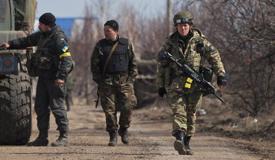 Ukraine servicemen walk at a front-line position east of Mariupol, Tuesday. President Obama has not ruled out providing defensive weapons, but administration officials offered no clue on when Mr. Obama might make a final decision. (Associated Press)