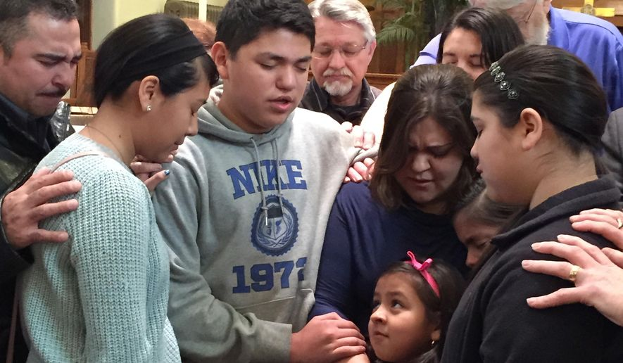 Gloria Villatoro joins her children, friends and community members in prayer at the Trinity United Methodist Church in Des Moines, Iowa, Tuesday, March 10, 2015. Villatoro was traveling to the Omaha Immigration and Customs Enforcement office to deliver 25,518 petitions, calling for the release of her husband, Max Villatoro, who was arrested by immigration officials last week and now faces deportation for a 17-year-old drunken driving conviction. (AP Photo/Kourtney Liepelt)