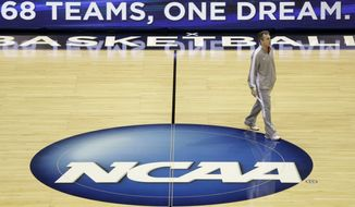 American University head coach Mike Brennan walks around the court during a practice session for their NCAA college basketball tournament game Wednesday, March 19, 2014, in Milwaukee. American plays Wisconsin in round two on Thursday. (AP Photo/Morry Gash)