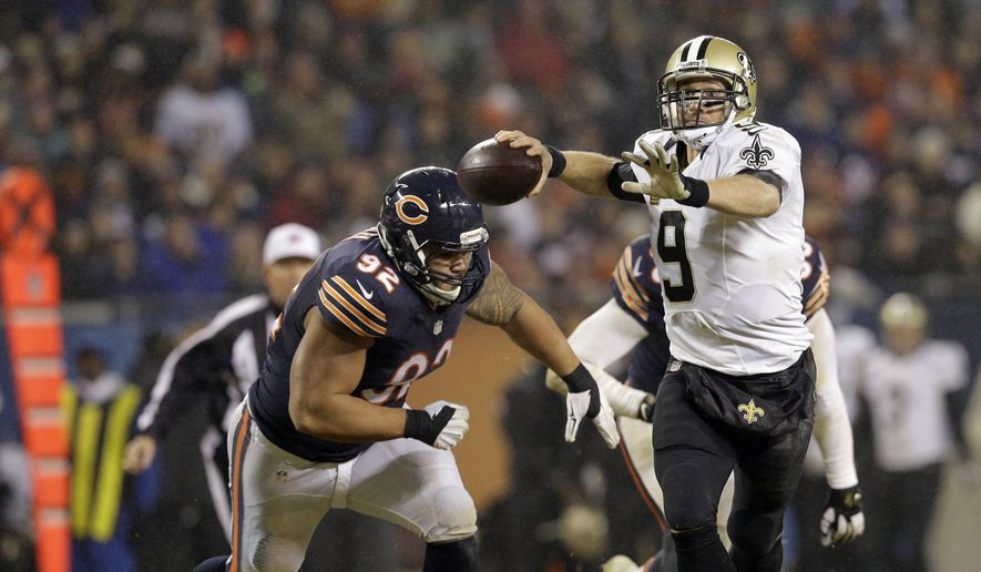 New Orleans Saints quarterback Drew Brees (9) throws a pass against Chicago Bears defensive tackle Stephen Paea (92) during the second half of an NFL football game Monday, Dec. 15, 2014, in Chicago. (AP Photo/Nam Y. Huh)