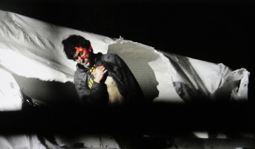 In this photo provided by the Massachusetts State Police, Boston Marathon bombing suspect Dzhokhar Tsarnaev, bloody and disheveled with the red dot of a sniper's rifle laser sight on his head, emerges from a boat at the time of his capture by law enforcement authorities in Watertown, Mass., on April 19, 2013. (Associated Press/Massachusetts State Police, Sean Murphy) **FILE**