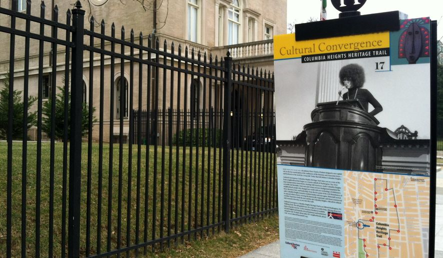 This Feb. 9, 2015 photo shows a street sign in the Columbia Heights section of Washington, D.C., marking the site of All Souls Church, where activist Angela Davis spoke in 1974. The sign is one of 19 marking historic and noteworthy spots around the neighborhood, which has made a comeback in recent years. (AP Photo/Beth J. Harpaz)