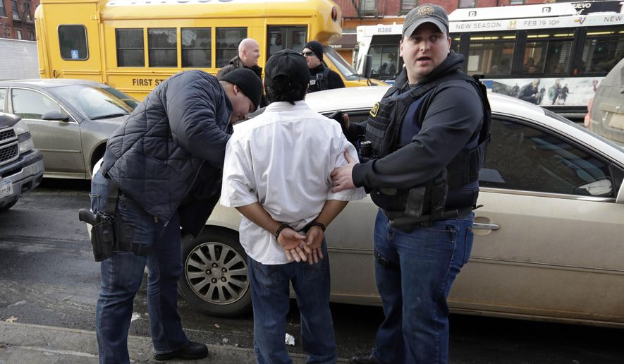 In this March 3, 2015 photo, Immigration and Customs Enforcement officers make an arrest in New York, during a series of early-morning raids. Immigrant and Customs Enforcement say an increasing number of cities and counties across the United States are limiting cooperation with the agency.  (AP Photo/Richard Drew)