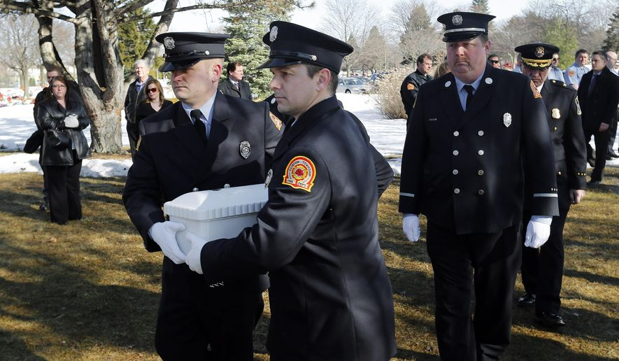 Members of the Clinton Township fire department carry the casket of a newborn, known simply as Baby Henry, at the funeral in Clinton Township, Mich., Wednesday, March 11, 2015. A fire department honor guard, local leaders and members of the public attended to pay their respects to Baby Henry whose lifeless body was discovered almost two months ago at a Detroit-area recycling center. Police say 24-year-old Angela Alexie gave birth Dec. 22 in an Eastpointe garage and left the baby. The body was found Jan. 14 at a Roseville recycling center. Alexie is charged with murder. (AP Photo/Paul Sancya)