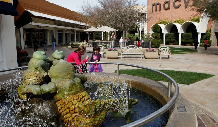 A woman and a young girl stand at a fountain at the Stanford Shopping Center, a Simon Property Group property, in Palo Alto, California. Analysts say the unsolicited $22.4 billion offer by Simon to acquire Macerich Co., reflects the attractiveness of upscale malls while more down-market properties struggle to adapt and survive. (Associated Press)