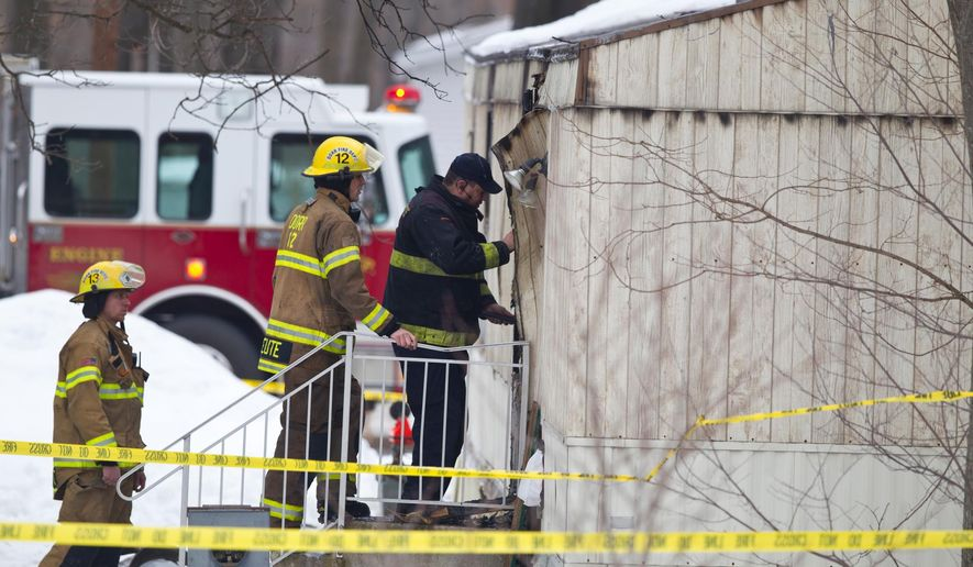 Emergency personnel investigate the scene of a fatal fire in Dorr Township, Mich., on Tuesday, March 10, 2015.   Police are seeking a homicide charge after bodies of an adult and two children were found following a suspicious mobile home fire.  Michigan State Police records show a warrant request for a man who lived at the home in Dorr Township, about 15 miles southwest of Grand Rapids. (AP Photo/The Grand Rapids Press, Joel Bissell ) ALL LOCAL TELEVISION OUT; LOCAL TELEVISION INTERNET OUT