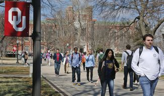 People walk on the Oval at the University of Oklahoma in Norman, Okla., Tuesday, March 10, 2015. (AP Photo/Sue Ogrocki)