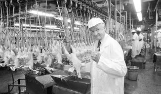 Owner Frank Perdue gives a thumbs up to the freshly plucked chickens travelling the production line in his Salisbury, Md., plant, on July 30, 1984. (AP Photo/Dan Miller)
