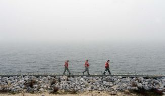 Unidentified military personnel walk along a causeway near Navarre Beach, Fla. Wednesday, March 11, 2015 as they search for survivors of an Army Black Hawk helicopter that went down Tuesday evening with 11 service members aboard.  (AP Photo/Northwest Florida Daily News, Devon Ravine)