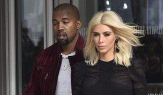 Kim Kardashian and singer Kanye West leave Louis Vuitton's Fall-Winter ready-to-wear fashion collection presented during the Paris Fashion Week, Wednesday, March 11, 2015 in Paris, France. (AP Photo/Zacharie Scheurer)
