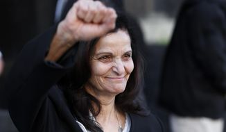 Rasmea Odeh raises her fist as she leaves federal court in Detroit Thursday, March 12, 2015. A judge sentenced the Chicago activist to 18 months in federal prison Thursday for failing to disclose her convictions for bombings in Israel when she applied to be a U.S. citizen. Odeh, 67, also was stripped of her citizenship and eventually will be deported. But she will remain free while she appeals the case. (AP Photo/Paul Sancya)