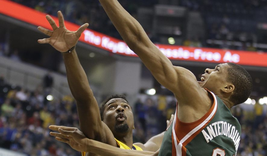 Milwaukee Bucks' Giannis Antetokounmpo (34) puts up a shot against Indiana Pacers' Solomon Hill (44) during the first half of an NBA basketball game Thursday, March 12, 2015, in Indianapolis. (AP Photo/Darron Cummings)