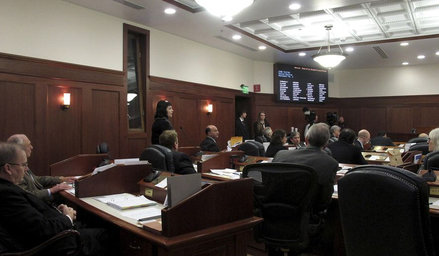 Rep. Shelley Hughes, R-Palmer, left standing, speaks on the House floor to a proposed amendment to the operating budget that would have added back provisions related to Medicaid expansion on Thursday, March 12, 2015, in Juneau, Alaska. The amendment, led by minority Democrats, failed. (AP Photo/Becky Bohrer)