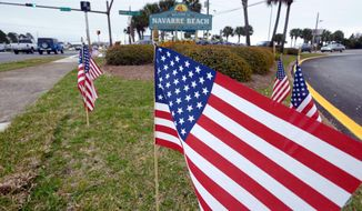 American flags stand in the median near the bridge entrance to Navarre Beach, Fla., Thursday, March 12, 2015 (AP Photo/Northwest Florida Daily News, Devon Ravine)