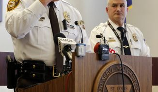 St. Louis County police Chief Jon Belmar, left, describes where one officer was shot on his face as Webster Groves police Captain Mike Nelson listens during a news conference Thursday, March 12, 2015, in Ferguson, Mo. Belmar spoke about the two officers who were shot, one from the St. Louis County police department and one from Webster Groves, in front of the Ferguson Police Department early Thursday as demonstrators gathered. (AP Photo/Jeff Roberson)