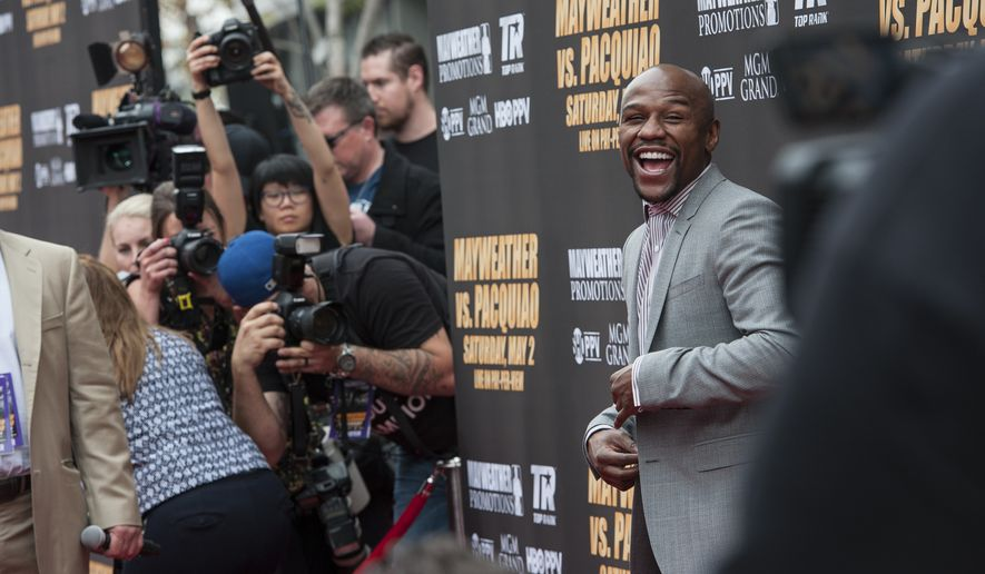 Floyd Mayweather Jr., enters the red carpet before a news conference in Los Angeles on Wednesday, March 11, 2015. Mayweather is scheduled to fight Manny Pacquiao on May 2, in Las Vegas. (AP Photo/The Orange County Register, Ed Crisostomo) //ADDITIONAL INFORMATION: harmonson.0312ñ 03/11/15 ñ ED CRISOSTOMO, ORANGE COUNTY REGISTER- Column on the spectacle surrounding the first (and likely only) news conference in advance of the Floyd Mayweather Jr.-Manny Pacquiao fight. The fighters are scheduled to arrive on the red carpet outside Nokia Theatre at L.A. LIVE at 11 a.m. After interview sessions, there will be a big news conference in the theater itself. The plan is to write about how big an event they are making of this and, if this is the starting point, what is the fight going to turn into?