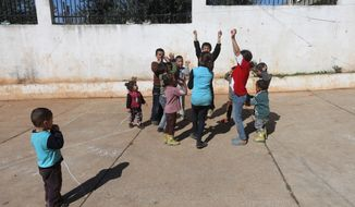 In this photo taken Friday, March 6, 2015, Syrian refugee children play in the backyard of the Al-Rama Public School that has become home to 22 Syrian families int the Lebanese-Syrian border village of Al-Rama, north Lebanon. (AP Photo/Hussein Malla)