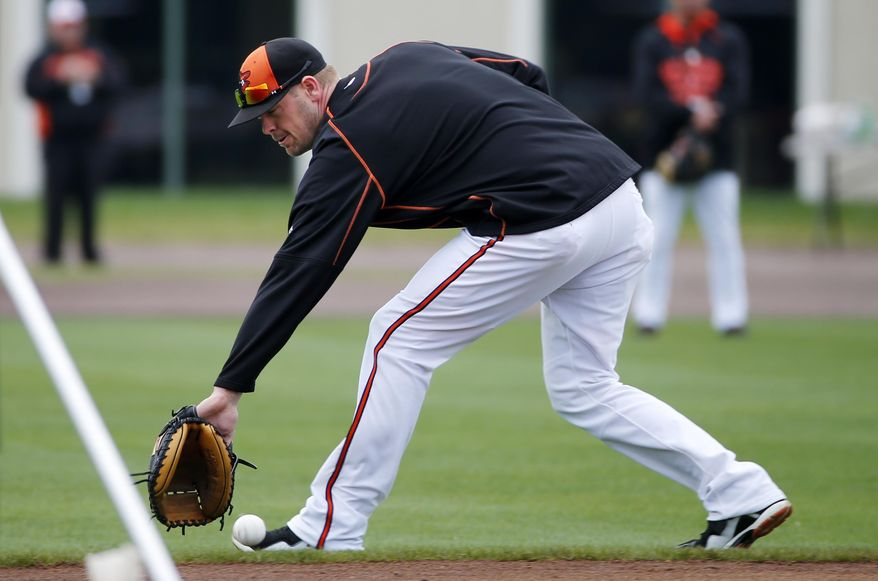 Baltimore Orioles catcher Matt Wieters backhands a ground ball during batting practice before a spring training exhibition baseball game against the Boston Red Sox in Sarasota, Fla., Saturday, March 7, 2015.  (AP Photo/Gene J. Puskar)