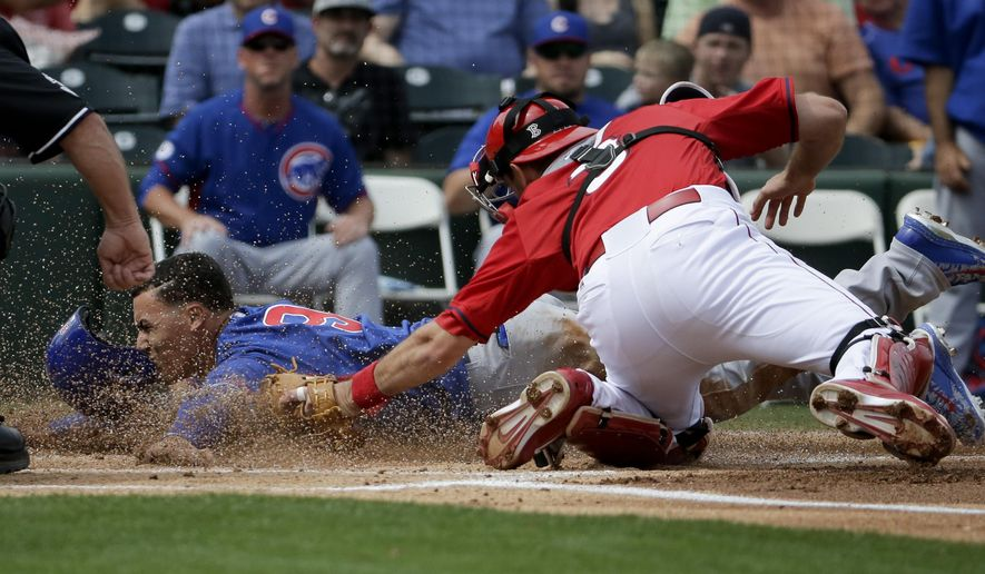 Chicago Cubs' Javier Baez, left, scores past Los Angeles Angels catcher Drew Butera during the first inning of a spring training baseball exhibition game in Tempe, Ariz., on Thursday, March 12, 2015. (AP Photo/Chris Carlson)