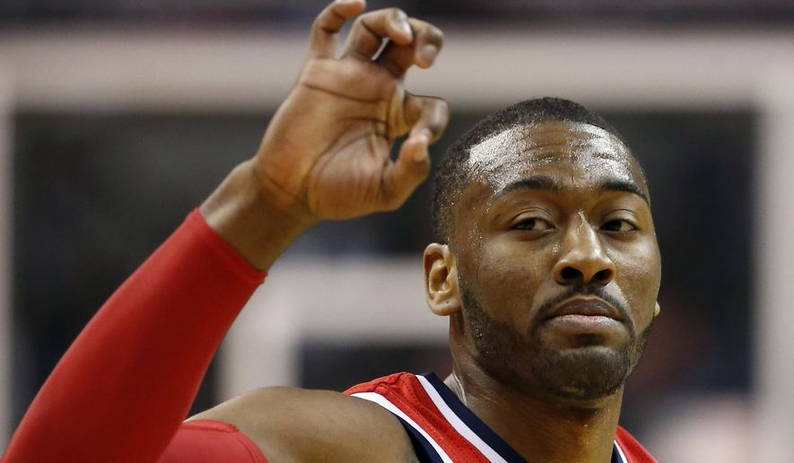 Washington Wizards guard John Wall celebrate a 3-point shot by forward Paul Pierce in the first half of an NBA basketball game against the Memphis Grizzlies, Thursday, March 12, 2015, in Washington. (AP Photo/Alex Brandon)