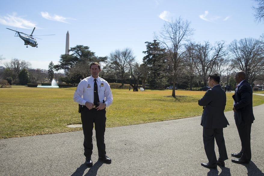 A Secret Service officer and Secret Service agents provide security as Marine One carries President Barack Obama off the South Lawn of the White House, on Thursday, March 12, 2015, in Washington. Obama to traveling to Los Angeles for an appearance on Jimmy Kimmel Live, and a DNC fundraiser. (AP Photo/ Evan Vucci)