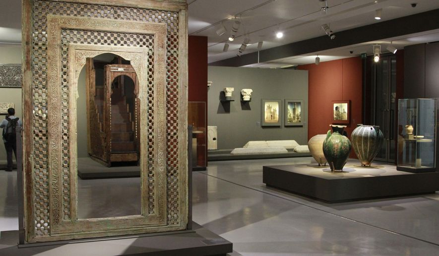 """This photo taken March 4, 2015 shows a carved wooden medieval doorway from the Moroccan city of Fez dominating the exhibition room at the Mohammed VI Museum of Modern and Contemporary art in Rabat, Morocco. The """"Medieval Morocco: An Empire of Africa and Spain"""" brings together Islamic Art from a dozen museums and will be exhibited in Rabat until June 3. (AP Photo/ Paul Schemm)"""