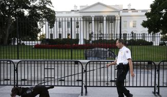 A member of the Secret Service Uniformed Division with a K-9 walks along the perimeter fence along Pennsylvania Avenue outside the White House in Washington, Sept. 22, 2014. (Associated Press) ** FILE **