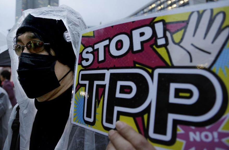 FILE - In this April 22, 2014 file photo, a protester holds a placard during a rally against the Trans-Pacific Partnership (TPP) in Tokyo. The United States is negotiating the ambitious trade agreement with 11 other Pacific Rim countries that's meant to ease barriers to fast-growing Asia-Pacific markets and streamline customs rules. (AP Photo/Shizuo Kambayashi, File)