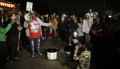 Protesters in Ferguson, Mo., gather across the street from the Ferguson Police Department following the resignation of the city's police chief in the wake of a U.S. Justice Department report. (AP Photo/Jeff Roberson)