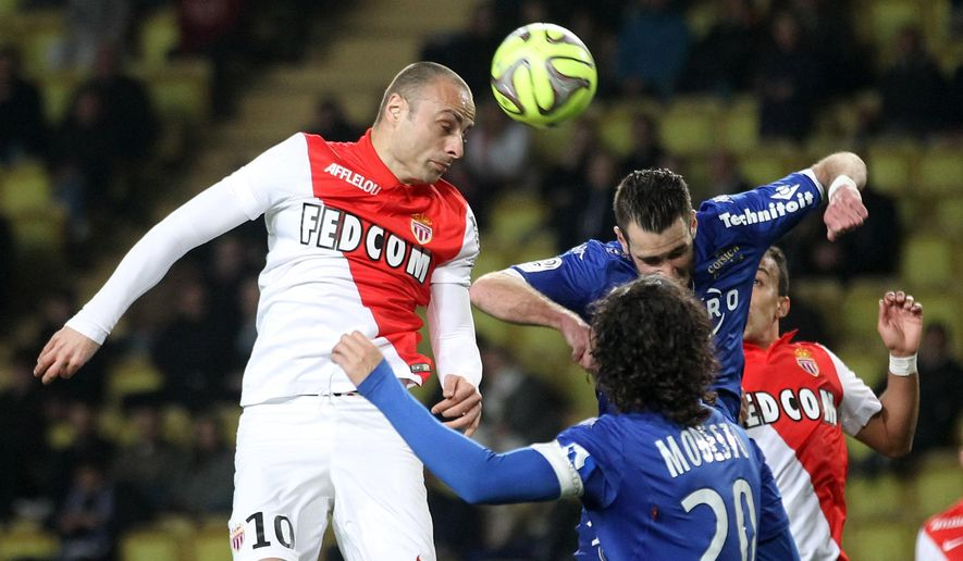 Monaco's Dimitar Berbatov, left, challenges for the ball with  Bastia's Francois Modesto, down and BFlorian Marange during their French League One soccer match, in Monaco stadium, Friday, March 13, 2015. (AP Photo/Lionel Cironneau)