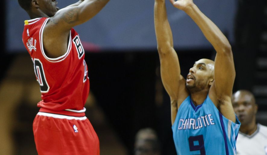 Chicago Bulls forward Tony Snell, left, shoots over Charlotte Hornets forward Gerald Henderson in the first half of an NBA basketball game Friday, March 13, 2015, in Charlotte, N.C. (AP Photo/Nell Redmond)