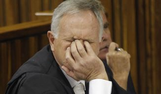 Barry Roux, defense lawyer for Oscar Pistorius, reacts in the High Court in Johannesburg Friday, March 13, 2015. Pistorius' lawyers failed in their attempt to stop prosecutors from appealing the double-amputee athlete's negligent killing conviction and again seeking a murder verdict against him for shooting girlfriend Reeva Steenkamp. (AP Photo/Kim Ludbrook, Pool.)