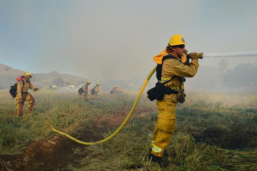 In this March 12, 2015 photo, Colby Morrison with the Ventura City Fire Department keeps the grass damp as a brush fire struggles to stay active along the Ventura River in Ventura, Calif. To the northwest, firefighters in Ventura County have been building containment lines around an approximately 22-acre blaze in vegetation in a riverbed. (AP Photo/The Ventura County Star, Karen Quincy Loberg) LOS ANGELES DAILY NEWS OUT