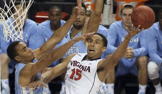 Virginia's Malcolm Brogdon (15) shoots against North Carolina's Brice Johnson, left, during the first half of an NCAA college basketball game in the semifinals of the Atlantic Coast Conference tournament in Greensboro, N.C., Friday, March 13, 2015. (AP Photo/Bob Jordan)