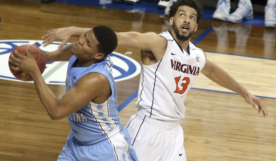 North Carolina's Kennedy Meeks, left, grabs a rebound in front of Virginia's Anthony Gill, right, during the second half of an NCAA college basketball game in the semifinals of the Atlantic Coast Conference tournament in Greensboro, N.C., Friday, March 13, 2015. North Carolina won 71-67. (AP Photo/Bob Jordan)