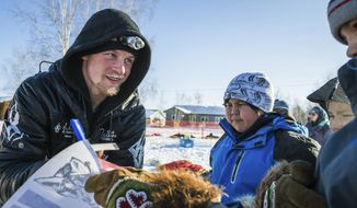 Dallas Seavey signs autographs at the Huslia, Alaska, checkpoint of the Iditarod Trail Sled Dog Race, Friday, March 13, 2015. (AP Photo/Alaska Dispatch News, Loren Holmes)