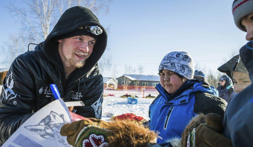Dallas Seavey signs autographs at the Huslia, Alaska, checkpoint of the Iditarod Trail Sled Dog Race, Friday, March 13, 2015. (AP Photo/Alaska Dispatch News, Loren Holmes)