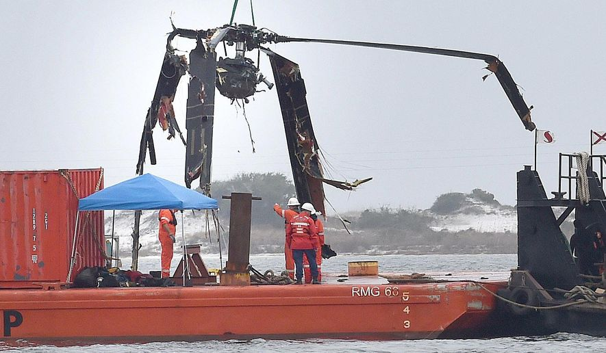 Crews lower a piece of a Black Hawk helicopter onto a barge in the Santa Rosa Sound near Pritchard Point, Friday, March 13, 2015, in Navarre, Fla. The helicopter, which crashed in dense fog during a training mission, was carrying seven Marines based in North Carolina along with four National Guard soldiers from Louisiana. All were killed. (AP Photo/Northwest Florida Daily News,  Nick Tomecek)