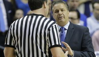 Kentucky head coach John Calipari speaks with an official during the first half of an NCAA college basketball game in the semifinal round of the Southeastern Conference tournament against Auburn, Saturday, March 14, 2015, in Nashville, Tenn. (AP Photo/Mark Humphrey)